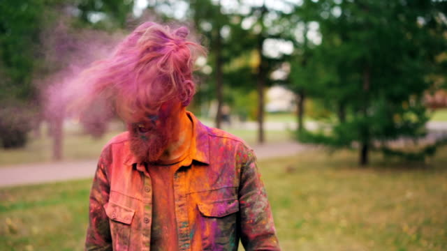 vídeos de stock e filmes b-roll de slow motion portrait of handsome young man with trendy hairstyle tossing his hair covered with bright holi paint powder, looking at camera and laughing. - holi