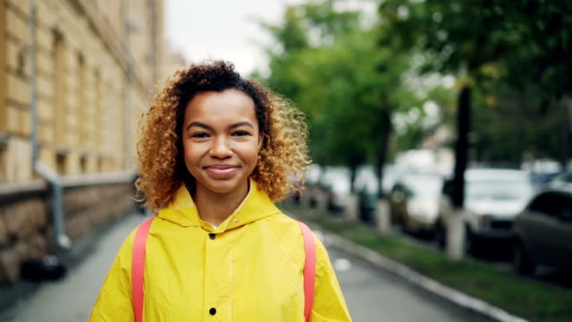 Slow motion portrait of happy African American girl smiling and looking at camera standing outdoors with green trees and beautiful buildings in background.