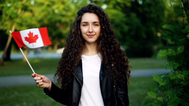 slow motion portrait of happy canadian sports fan waving national flag of canada looking at camera with glad smile while standing outside in park on summer day. - canada flag stock videos & royalty-free footage