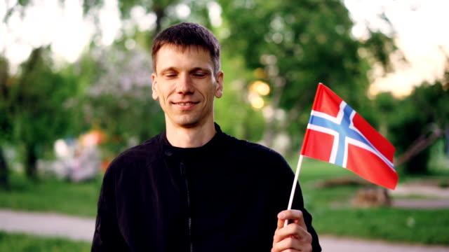 幸せのノルウェー学生を公式の国旗を保持して、カメラ目線と笑顔のスローモーションの肖像画。美しい緑豊かな公園は、バック グラウンドでです。 - 各国の観光地点の映像素材/bロール