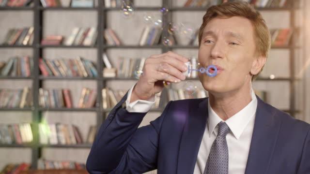 slow-motion portrait glücklich erfolgreicher jubelnden geschäftsmann luft seifenblasen. luftblasen im büro macht spaß. unternehmer-serie. - bizarr stock-videos und b-roll-filmmaterial