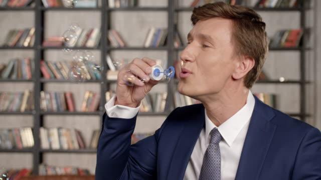 空気の泡を吹いて幸せ成功応援ビジネスマンのスローモーションの肖像画。オフィスで泡を作る楽しさを持っています。ビジネスマン シリーズ。 ビデオ