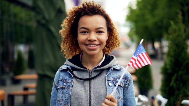 vidéos et rushes de slow motion portrait d'adolescente de fille assez afro-américaine regardant la caméra et tenant le drapeau américain, debout à l'extérieur de la ville moderne. concept de tourisme et les gens. - culture américaine