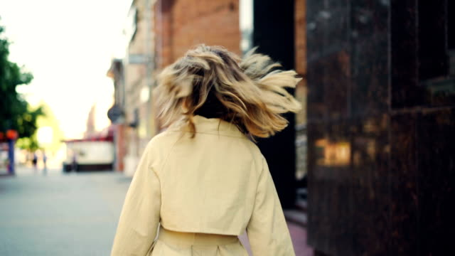 Slow motion portrait of smiling young woman in trendy coat walking in the street, turning to camera and looking at camera. Cheerful people, city and urban lifestyle concept.
