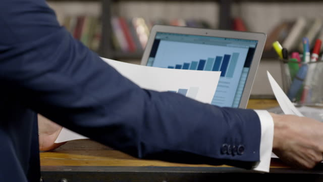 Slow Motion Portrait of Successful Businessman Flipping Through the Documents Sitting at the Table. Businessman Series. video