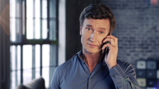 Slow Motion Portrait of Successful Businessman Talking on Smartphone at Office Smiling. Businessman Series. video
