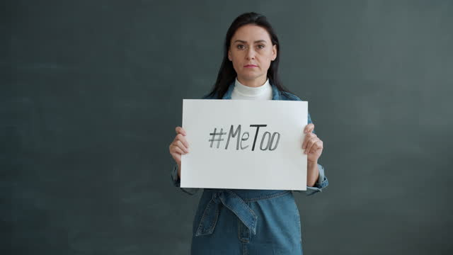 Slow motion portrait of woman holding MeToo hashtag banner and looking at camera standing alone video
