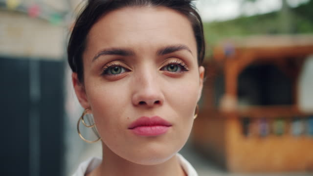 slow motion portrait of young adult woman with serious face standing outdoors - trentenne video stock e b–roll