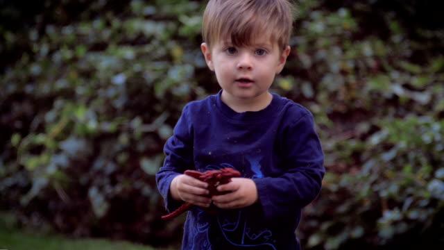 Toma en cámara lenta Retrato de linda joven niño con un juguete de dinosaurio de plástico - vídeo
