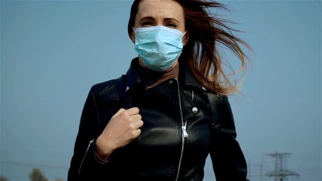 Slow motion porträtt ung kvinna i skyddande medicinsk mask som drivs av väg under blå himmel medan coronavirus epidemi video