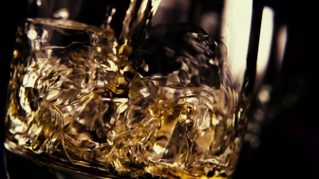 slow motion pour bourbon into a glass of ice - scotch whisky video stock e b–roll