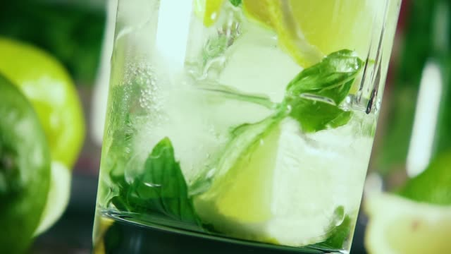 slow motion pour vodka into a glass with ice, citrus and mint - vodka video stock e b–roll