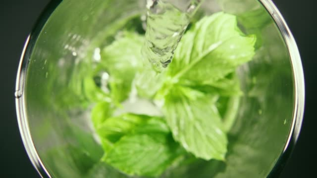 Slow motion pour water into a glass with mint and ice top view