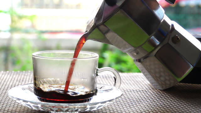 Slow motion ,Pouring freshly brewed black coffee with steam. video