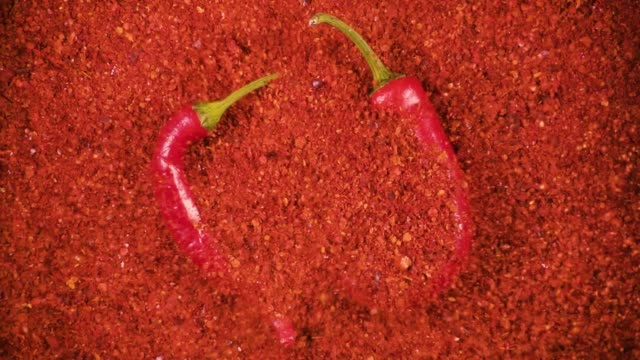 Slow motion powder falls on pepper top view Slow motion chili powder falls on two red peppers on the background of chili powder top view chili pepper stock videos & royalty-free footage