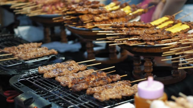 Slow motion, preparing small delicious kebabs on the hot grill. Traditional food street market in Thailand