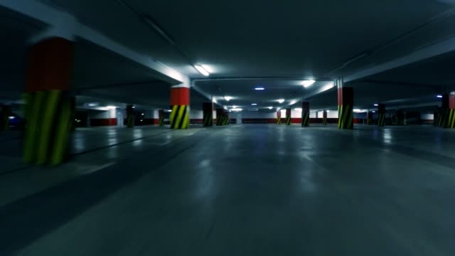 Slow motion: racing drone flying low in parking garage, point of view