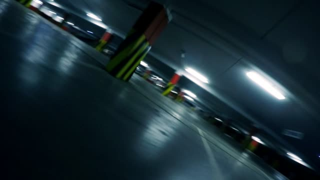 slow motion: racing drone flying low in parking garage, point of view - quadcopter filmów i materiałów b-roll