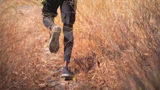 HD Slow Motion rear view tracking shot of Athlete trail runner man's legs are running on mountain trail. Sport man in sport clothes do outdoors sport training workout for strong and healthy lifestyle.