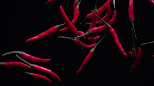 Slow motion red chilli on black background