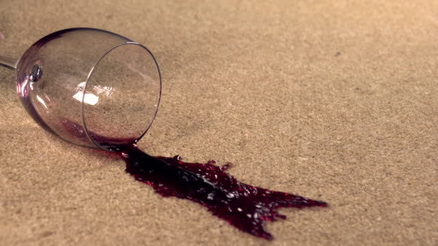 Slow motion red wine spilling on carpet