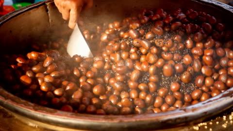 slow motion: castagne arrosto in un mercato alimentare - marrone video stock e b–roll