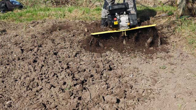 Slow motion rotary tiller blades loosen soil, ground scatters from cutter wheel. video
