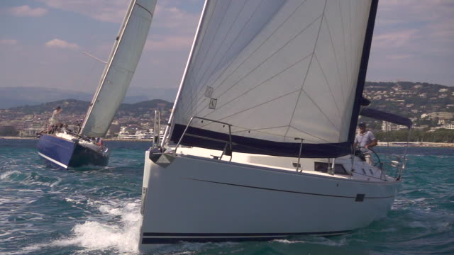 Slow motion sailing - yacht on gentle seas, slo mo Two sailing boats cut through the water on the sea in super slow motion. Off the coast of Cannes. regatta stock videos & royalty-free footage