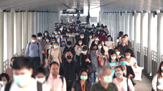 slow motion scene crowds of asian people wearing face protection in prevention for coronavirus or covid-19 and micro dust pm 2.5 in air while going to their workplace in bangkok at morning rush hour - zatłoczony filmów i materiałów b-roll