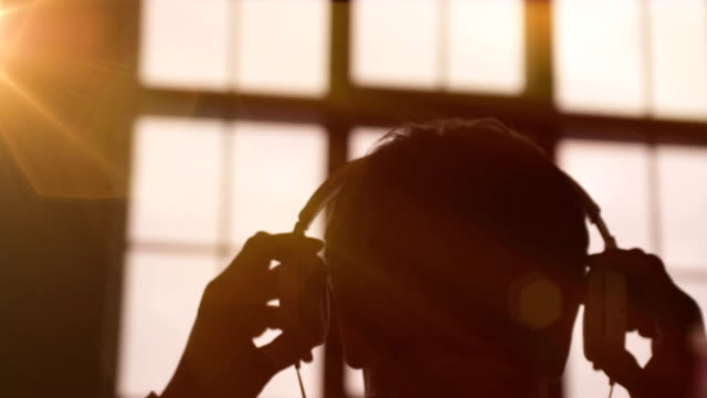 slow motion scene of a young attractive man wearing headphones at a window. listening music. sunset in the city. beautiful orange sun flares. - music filmów i materiałów b-roll