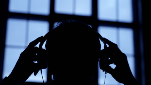 slow motion scene of a young attractive man wearing headphones at window evening. listening music. - cuffia attrezzatura per l'informazione video stock e b–roll