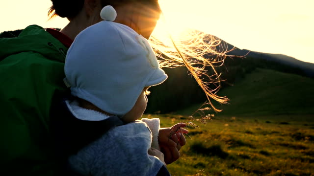 Slow motion scene of a young mother with a baby boy on a sunset background in mountains video