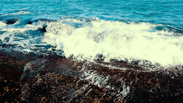 Slow motion sea waves crashing on stone beach video