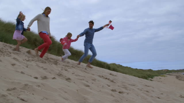 Slow motion sequence of family on beach holiday running through sand dunes together video