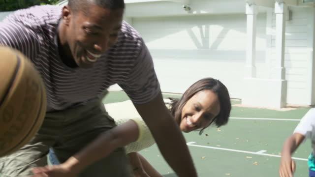 vídeos de stock, filmes e b-roll de câmera lenta sequência de família jogando basquete em casa - pai e filha