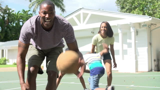 slow motion sequence of family playing basketball at home - basketball stock videos and b-roll footage