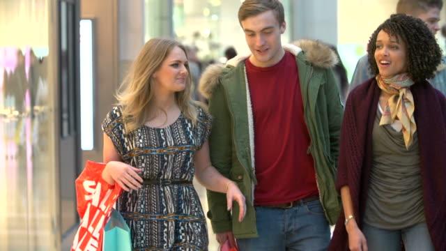 vídeos de stock, filmes e b-roll de câmera lenta sequência de amigos de compras juntos no shopping - shopping center