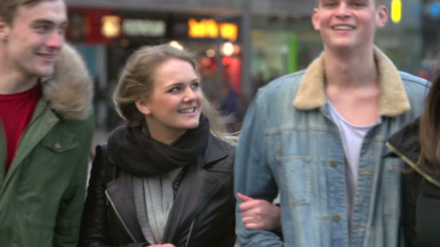 Slow Motion Sequence Of Friends Shopping Outdoors Together Slow motion sequence friends walking along shopping street together.Shot on Sony FS700 at frame rate of 200fps department store stock videos & royalty-free footage
