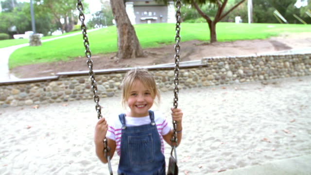 Slow Motion Sequence Of Girl On Swing In Playground Waving video