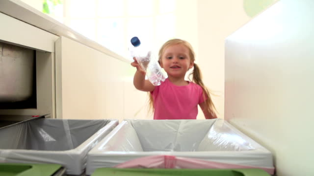 zwolnione tempo sekwencji dziewczyna w kuchni recyklingu odpadów w kosza - odzyskiwanie i przetwarzanie surowców wtórnych filmów i materiałów b-roll