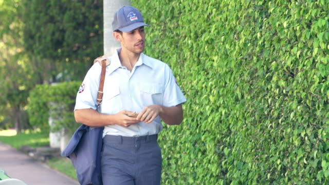 slow motion sequence of mail man delivering letters to woman - postal worker 個影片檔及 b 捲影像
