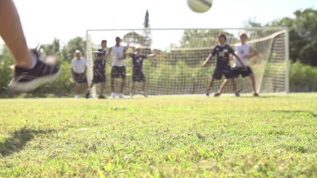 vídeos y material grabado en eventos de stock de cámara lenta la secuencia de escuela macho de puntuación objetivo del equipo de fútbol - deportes de la escuela secundaria
