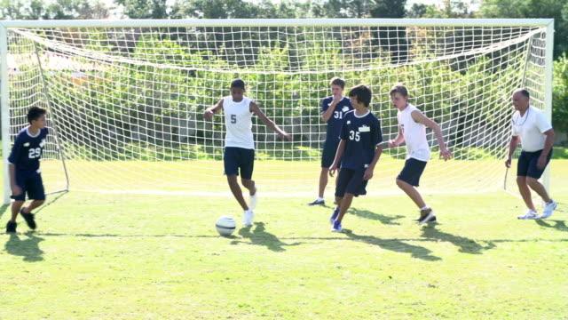vídeos y material grabado en eventos de stock de cámara lenta la secuencia de escuela macho de entrenamiento del equipo de fútbol - deportes de la escuela secundaria