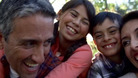 rallentatore sequenza di genitori dando bambini piggyback - etnia latino americana video stock e b–roll