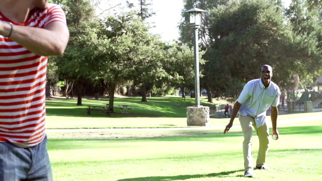 Slow Motion Sequence Of Two Men Playing Baseball In Park video
