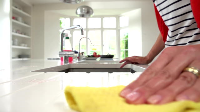 Slow Motion Sequence Of Woman Cleaning Surface In Kitchen Slow motion sequence of woman cleaning kitchen surface with cloth. Shot on Sony FS700 in PAL format at a frame rate of 50fps cleaning stock videos & royalty-free footage