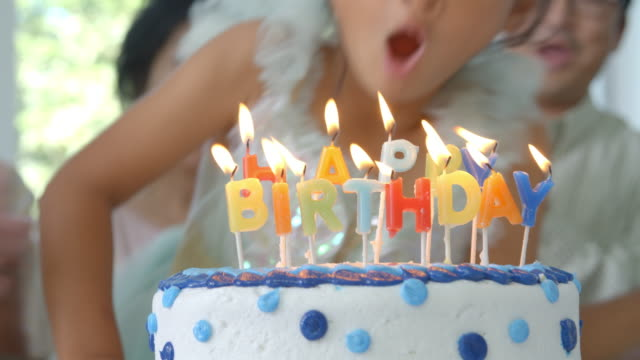 Slow Motion Shot As Girl Blows Out Candles On Birthday Cake video
