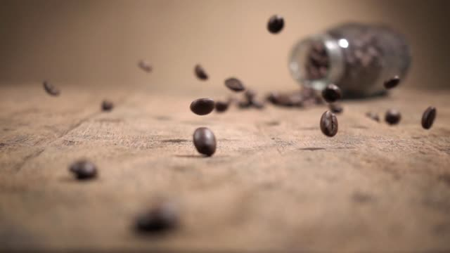 Slow Motion Shot Close Up Coffee Beans Falling On Wood Base