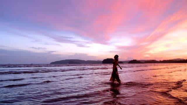 4 k スローモーション撮影: 夕陽が美しいビーチで一人で歩いて中年女性。 - サムイ島点の映像素材/bロール
