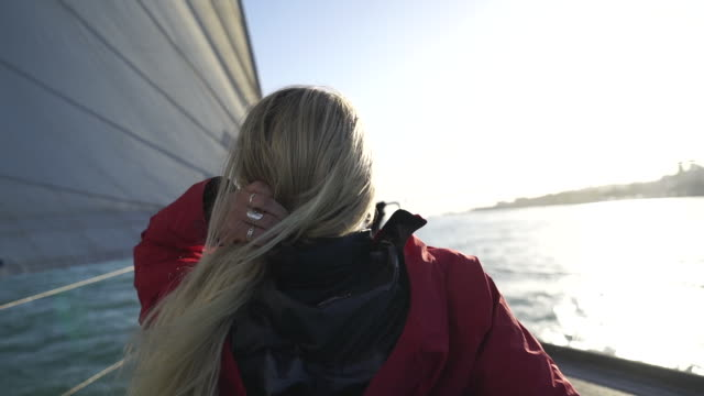 slow motion shot of a blond woman whipping her hair on a boat - эскапизм стоковые видео и кадры b-roll